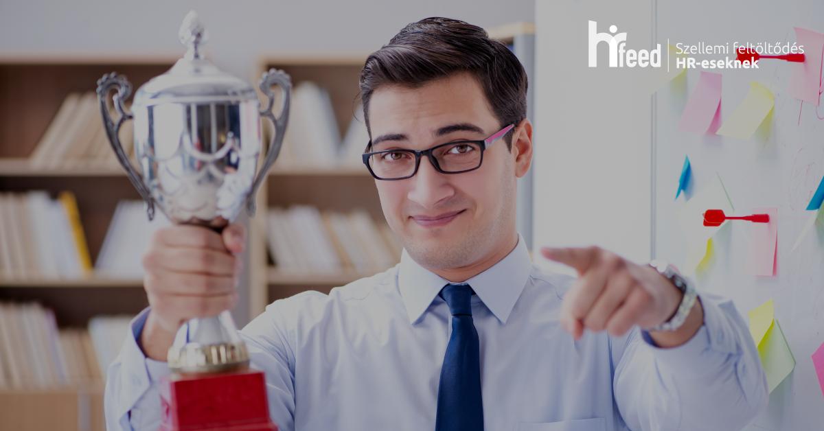 A képen egy munkavállalót láthatunk, aki büszkén tart egy serleget a kezében, rávilágítva arra, hogy milyen fontos a motiváció munkahelyen.